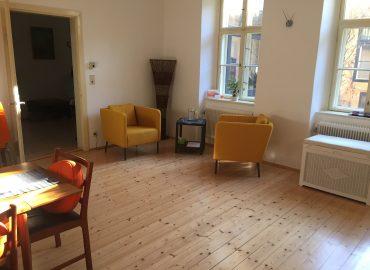 Ein Raum mit Parkettboden, weiße Wände, 2 gemütliche Stühle in gelb, Stehlampe, Beistelltisch, Tisch mit Stühlen