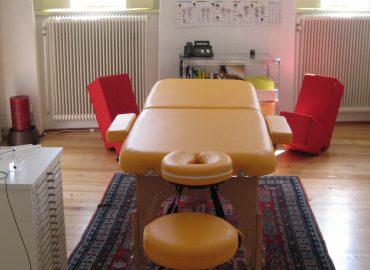 Raum mit Parkettboden, Behandlungsbett in gelb, darunter ein Teppich, rote Sitzgelegenheiten, ein Behandlungshocker in gelb