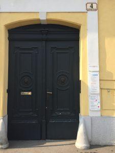 Eine hohe, doppeltürige Eingangstüre in dunkelgrün in einem gelb gehaltenen Haus