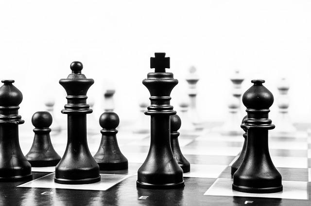 Schwarze Schachfiguren im Vordergrund, die weißen sind verschwommen im Hintergrund.