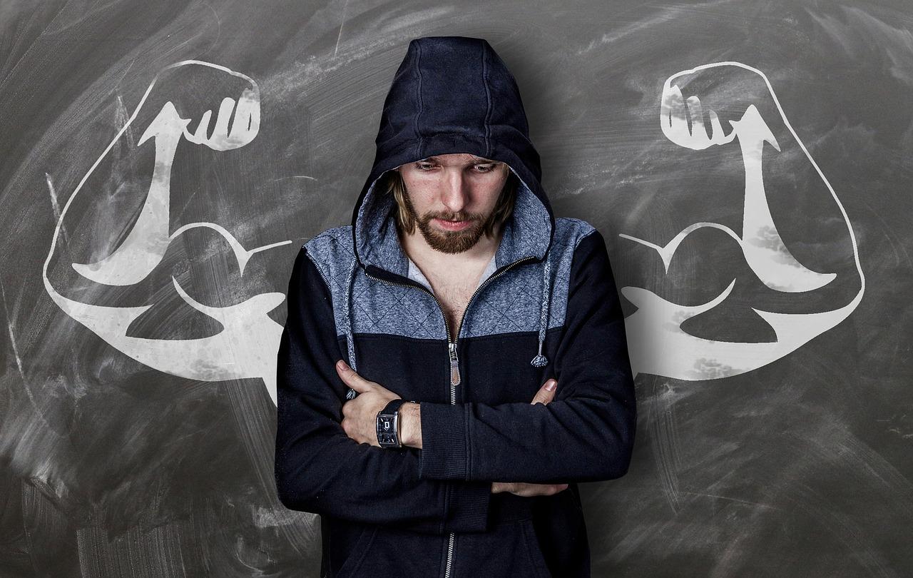 Ein Mann mit Kapuzenshirt steht mit verschränkten Armen und hängenden Kopf vor einer Schieferwand, wo 2 muskulöse Arme in angespannter Darstellung gezeichnet sind und so wirken, als ob der Mann die Arme anspannt