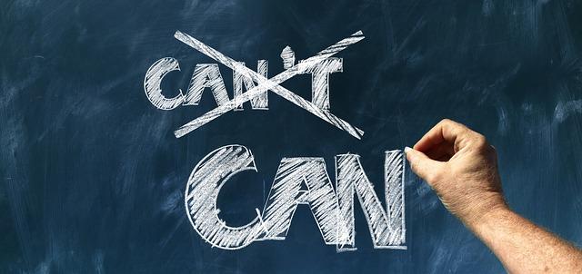 """Hand streicht auf einer Schiefertafel mit Kreide das Wort """"Can't"""" durch und schreibt darunter größer """"can"""""""