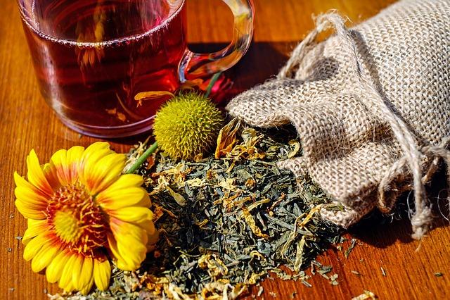 Jutesäckchen liegt offen auf einem Holztisch, davor div. getrocknete Kräuter und eine Pflanze. Ein Teehäferl mit einem rötlichen Tee steht daneben