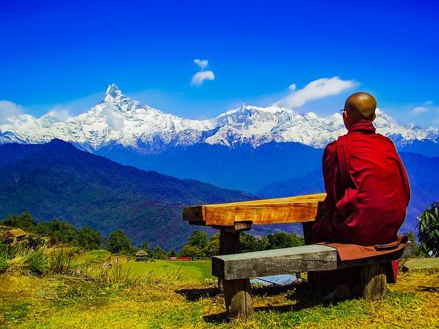 ein buddhistischer Mönch sitz auf einer Holzbank und blickt in ein schneebedecktes Gebirge
