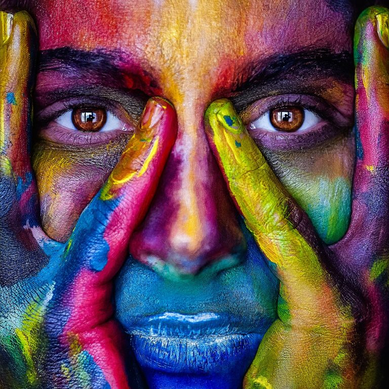 Ein Frauengesicht mit den beiden Händen im Gesicht, ganz bunt bemalt, Ringfinger und kleiner Finger um die Augen, die Augen geöffnet