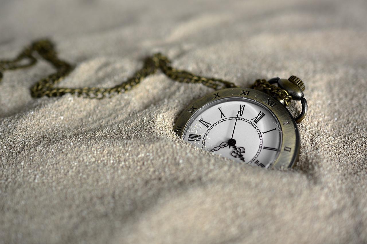 Eine Taschenuhr mit Kette, die zur Hälfte im Sand verschwunden ist