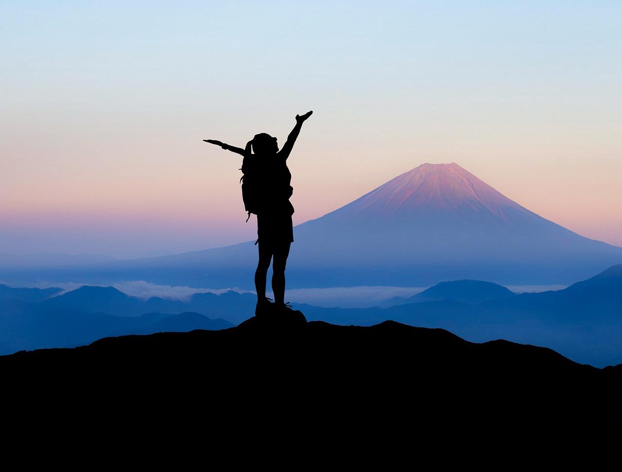 Eine Wanderin, die den Berggipfel erreicht hat und bei Arme in die Höhe streckt. Im Hintergrund ein Vulkan beim Sonnenuntergang