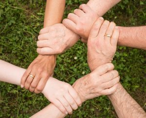 Arme von 6 Menschen, die sich jeweils auf das Handgelenk greifen und so einen Kreis bilden