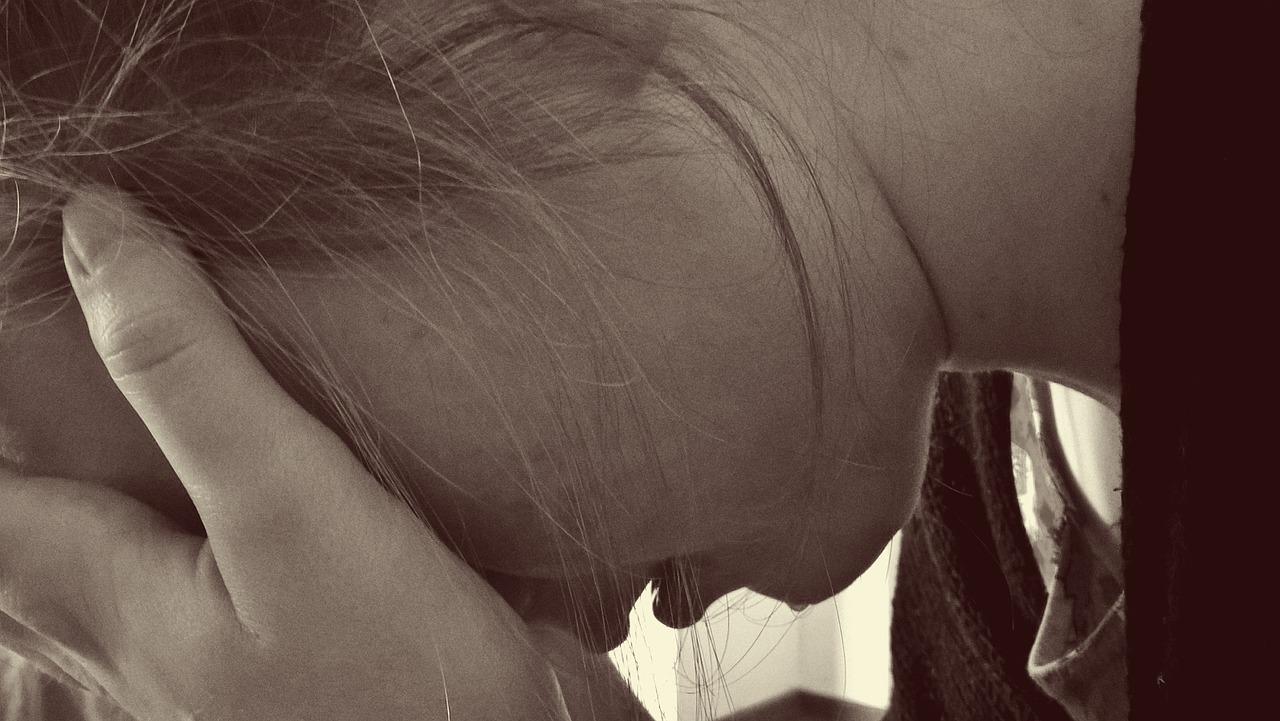 Abschnitt eines Seitenprofiles einer Frau, die Ihr Gesicht auf Ihre Hände stützt und verzweifelt wirkt